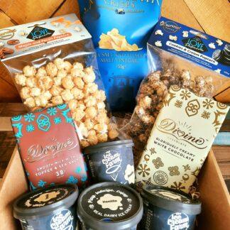 A box full of popcorn, ice cream, chocolate and crisps.